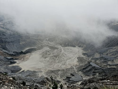 Rough volcanic crater with foamy hot water in mist