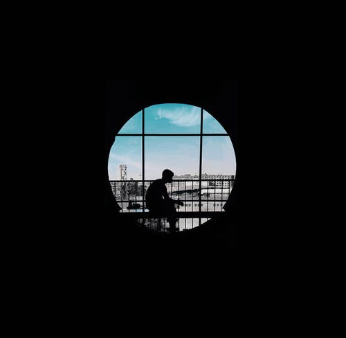 Silhouette of Person seated on Window Pane