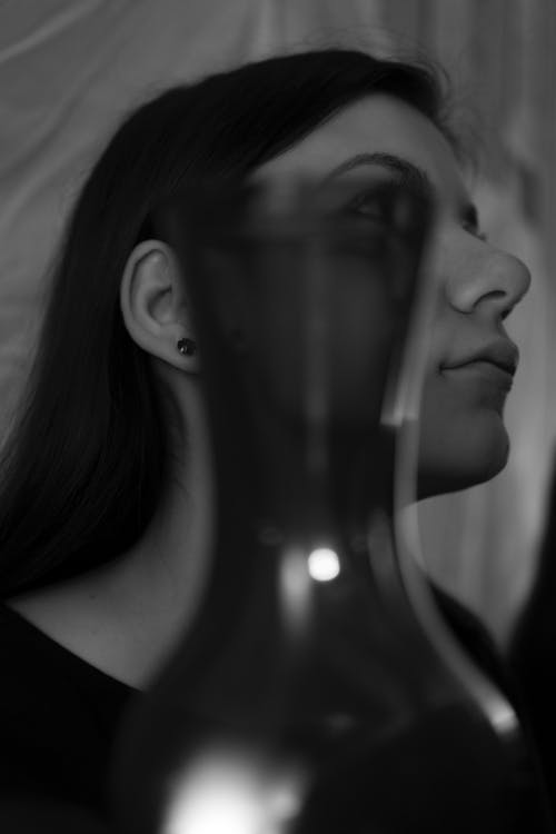 Calm young lady in dark room near glass vase