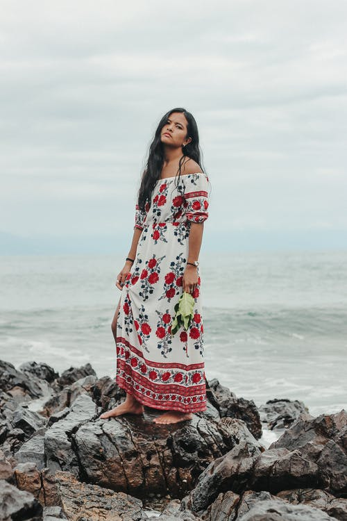 Full body thoughtful ethnic female wearing summer maxi dress standing on rocky coast near waving sea on cloudy day