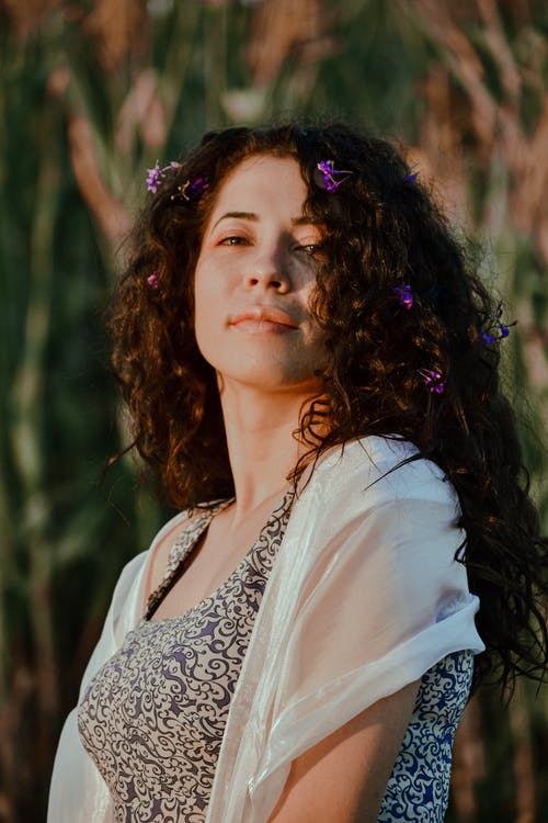 Charming woman with flowers in curly hair