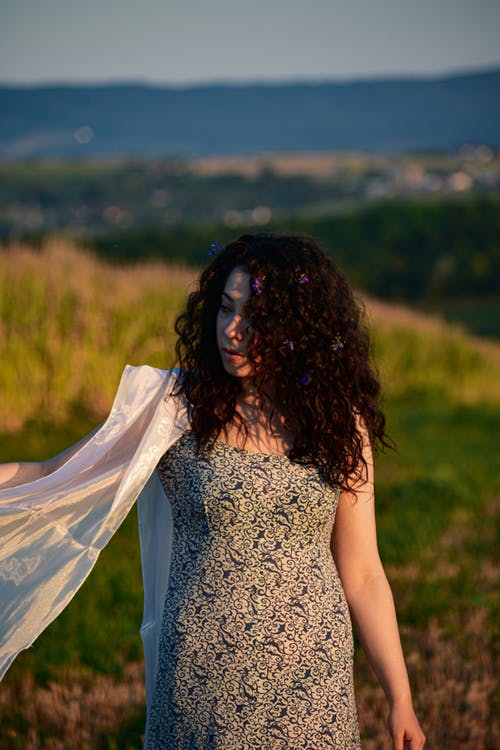 Young feminine lady in ornamental apparel with curly hair looking away on meadow behind mountain