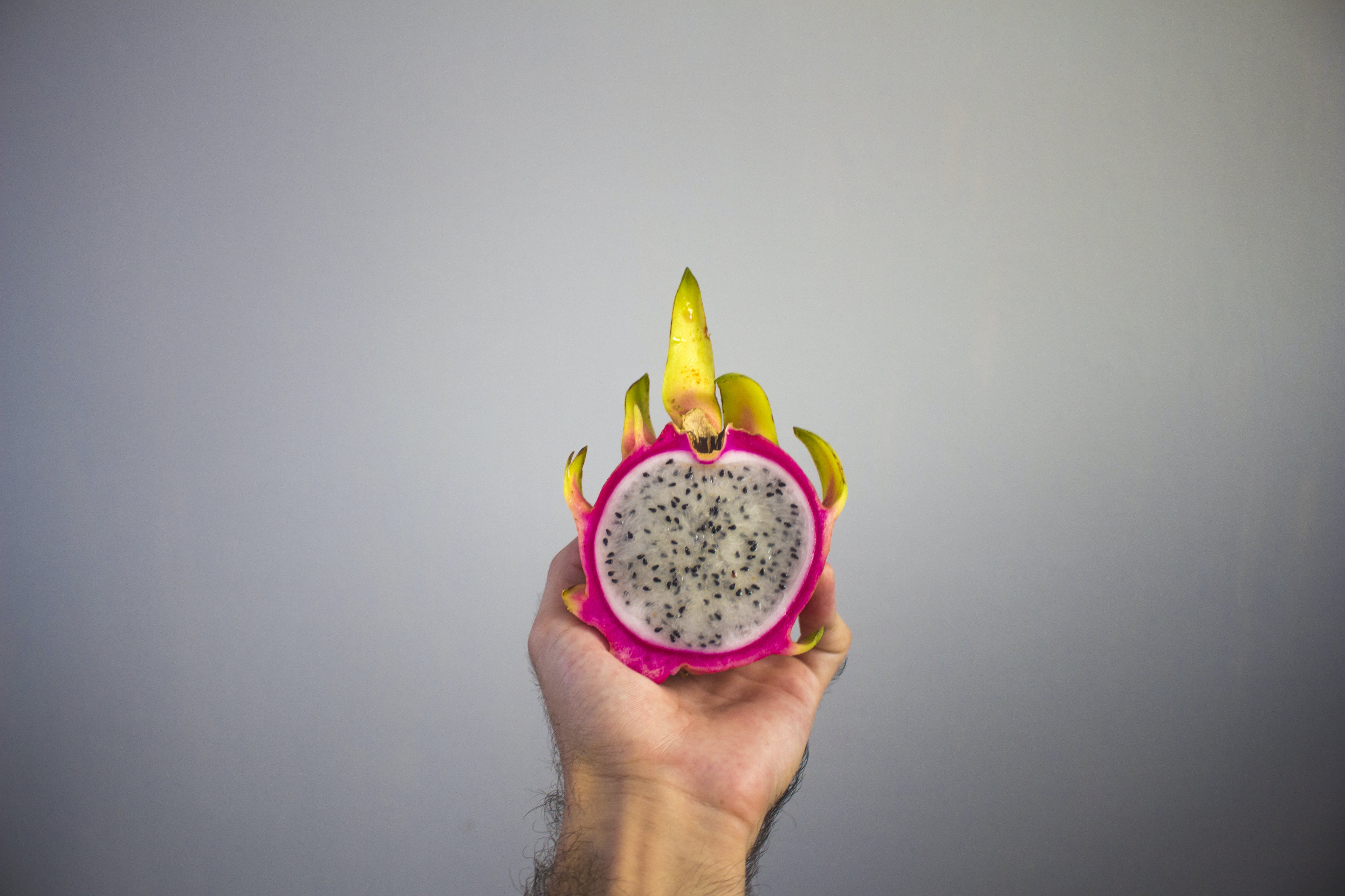 Person Holding Sliced Dragon Fruit