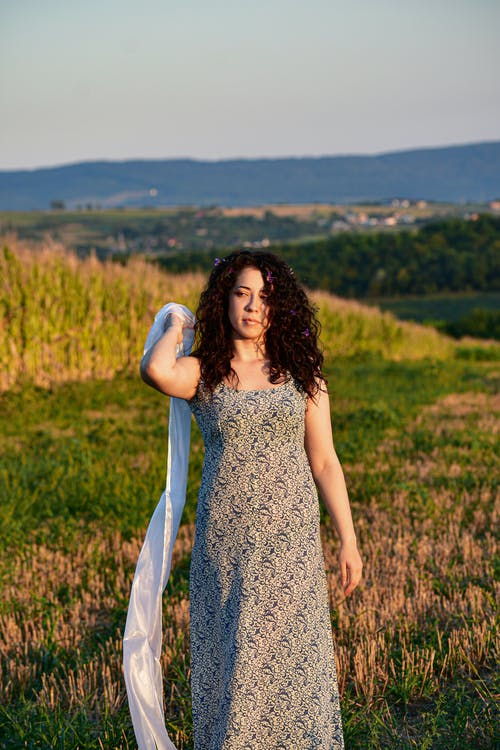 Young dreamy lady in sundress with chiffon scarf looking away in countryside in soft sunlight