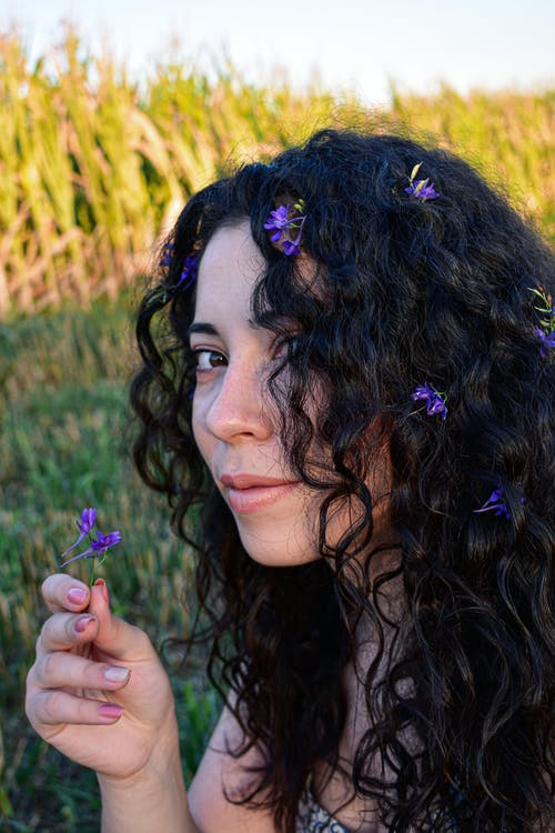 Positive woman with flowers in hair resting on grassy valley