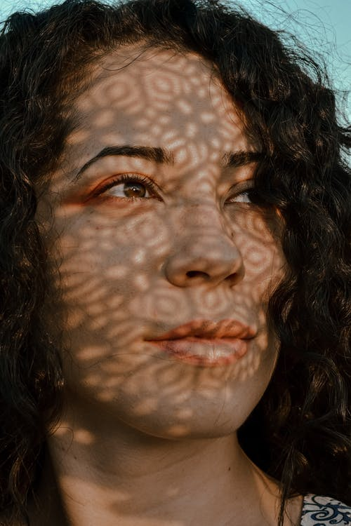 Crop glad female with black curly hair and shadows on face standing under blue sky and looking away dreamily