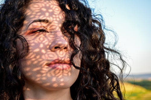 Crop sensitive female with long curly hair standing with shadow on face and looking away in dreams while spending warm day in countryside