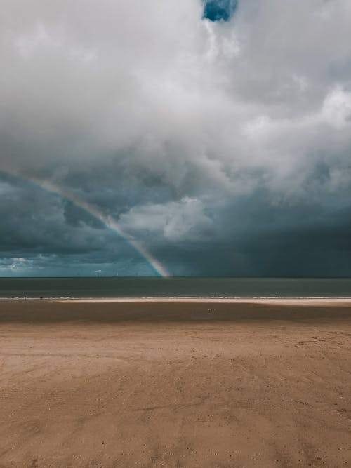 Wide sandy coast of sea under rainbow and clouds
