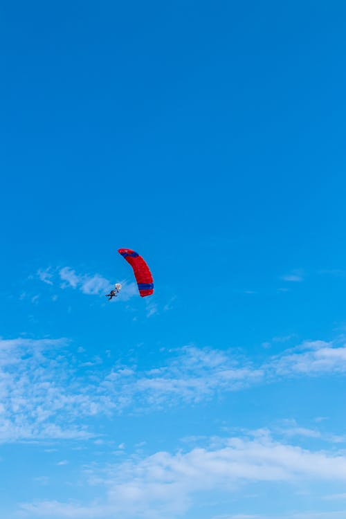 Person in Red Parachute in Mid Air