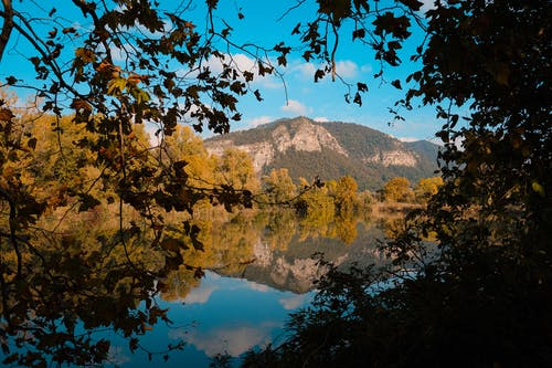 Picturesque scenery of calm lake reflecting mountains and trees with autumnal foliage in sunny day with blue cloudy sky