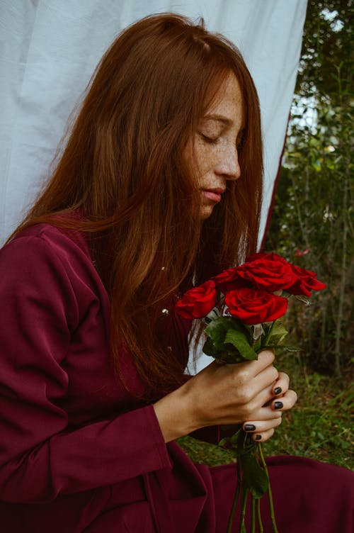 Side view of dreamy young female with long red hair and freckles in stylish outfit relaxing in green garden with bunch of red roses