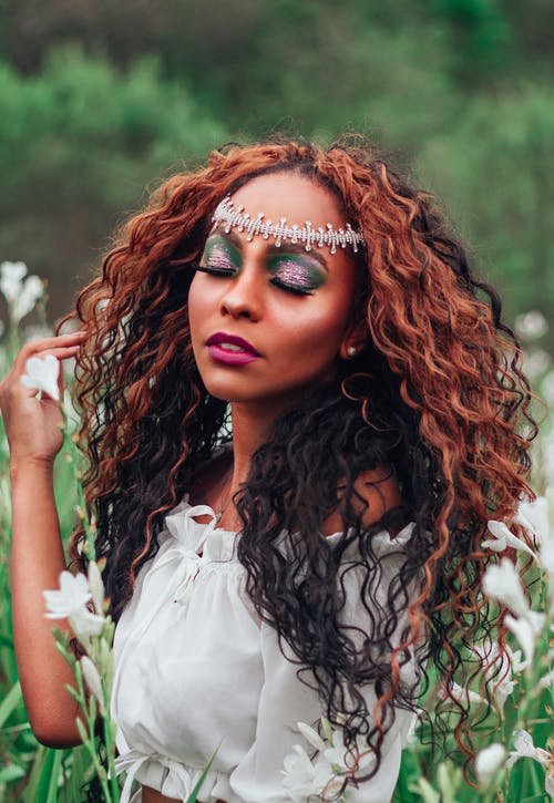 Tender ethnic female with curly hair and bright make up on closed eyes with tiara on forehead touching hair while standing in green field