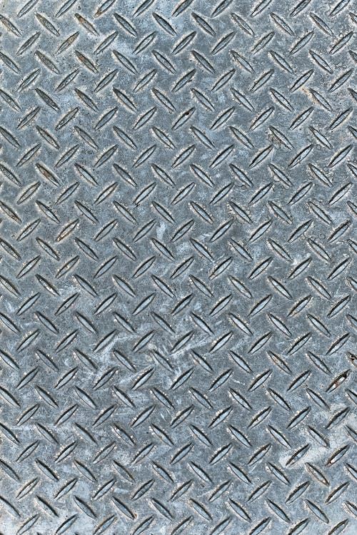 Background with gray steel plate with relief surface with fine repeating drop pattern of shabby metal structure with uneven texture
