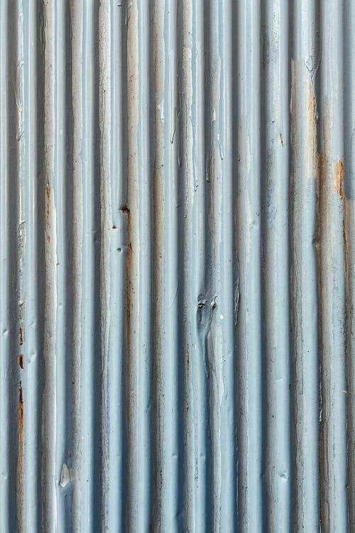 Background of old rusty metal wall with corrugated profile and relief texture with uneven gray surface and striped design outside
