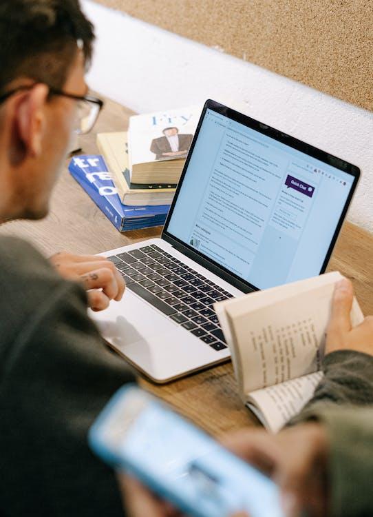 Man in Gray Sweater Using Macbook Pro