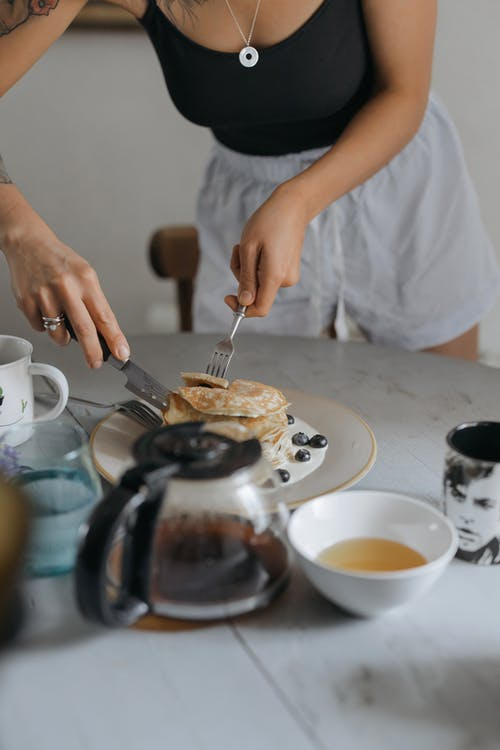 Person Eating Pancakes with Fresh Fruits