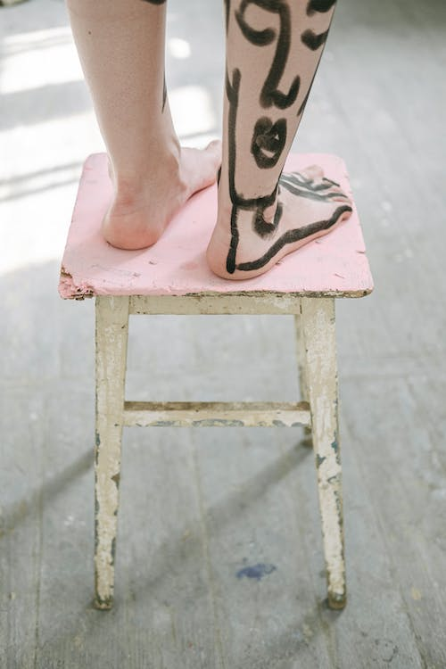 Person Standing on a Wooden Stool
