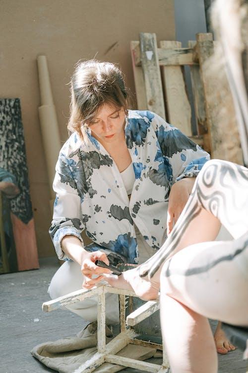 Woman in Tie-Dye Long Sleeve Shirt Holding a Black Marker