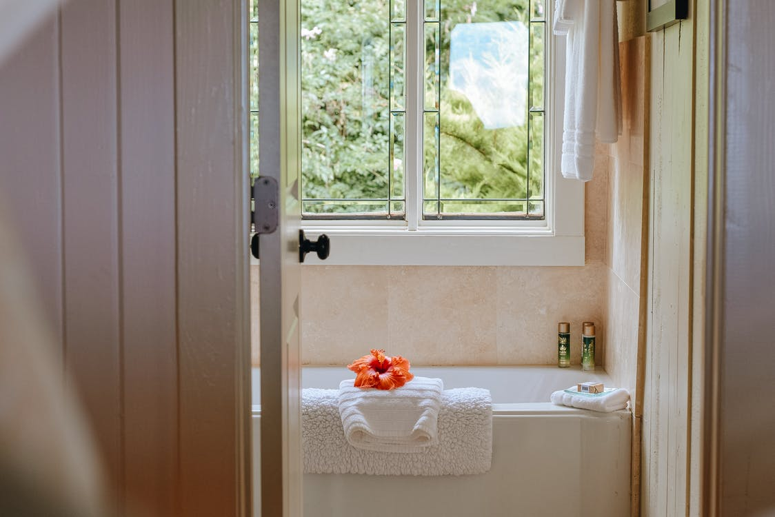 Clean light bathroom with window with view of green plants placed near bath in modern resort hotel