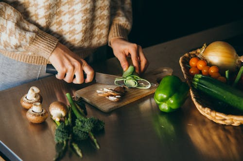 Person Slicing a Vegetable on Wooden Chopping Board