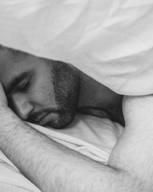 Serene man sleeping under blanket