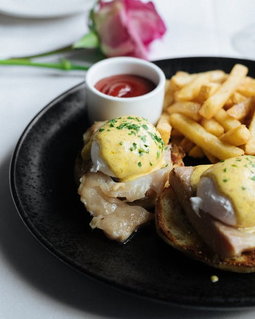 Eggs Benedict with French fries and salad dressing