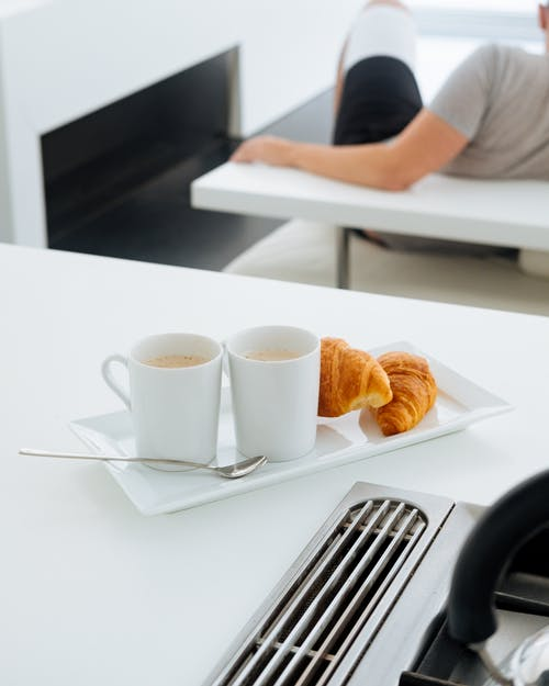 Croissants and cups of coffee on table in bright room