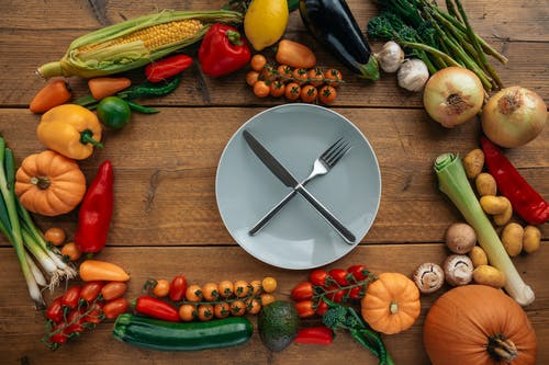Knife and Fork on a Ceramic Plate Surrounded by Assorted Vegetables
