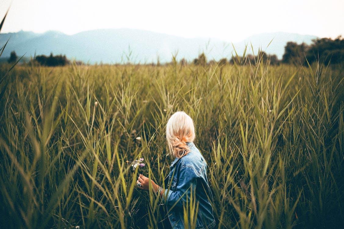 Person Wearing Blue Denim Jacket Looking Behind Grass Field