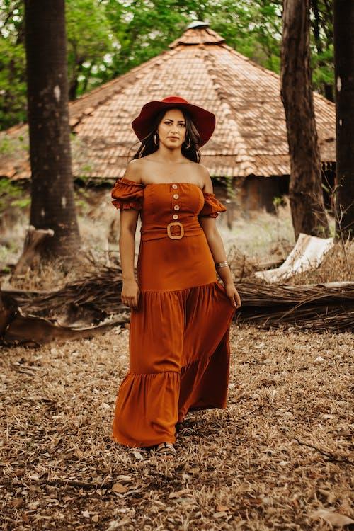 Woman in Orange Dress Standing Near Tree