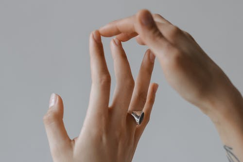 Person Wearing Silver Ring With Black Gemstone