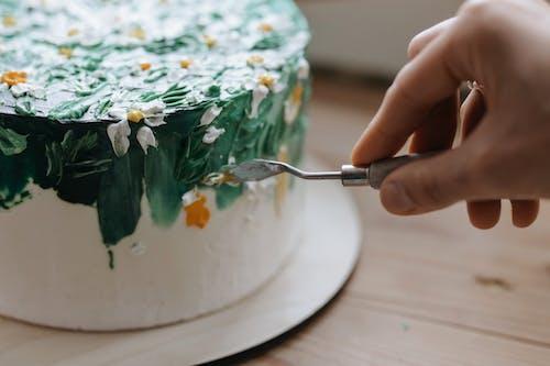 흰색 녹색과 주황색 꽃 케이크와 함께 실버 포크를 들고 사람