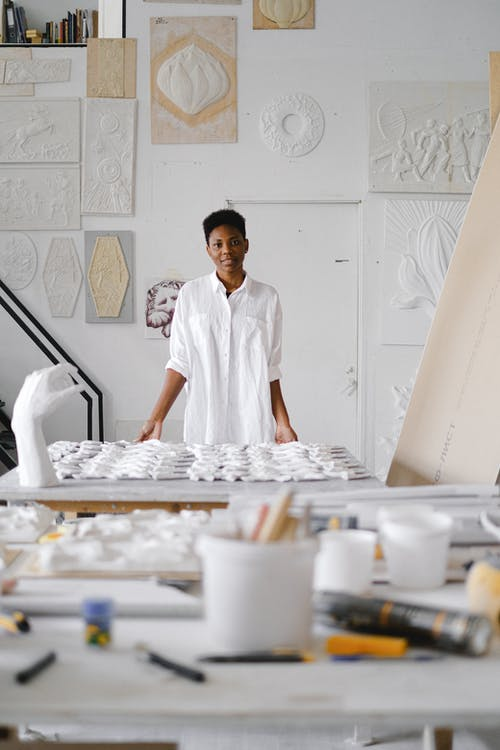 Person Standing Infront Of A Table With Ceramic Materials