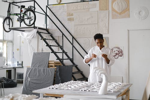 Person Standing Infront Of A Table With Ceramics