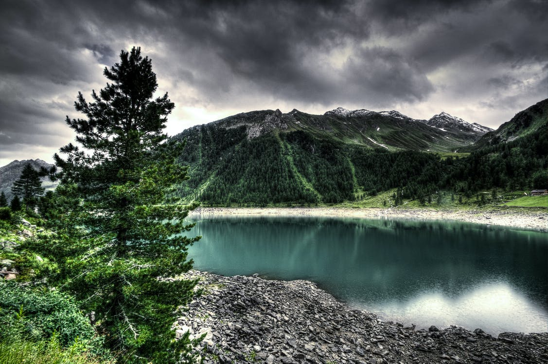 Body of Water Near Green Mountain Under Gray Clouds