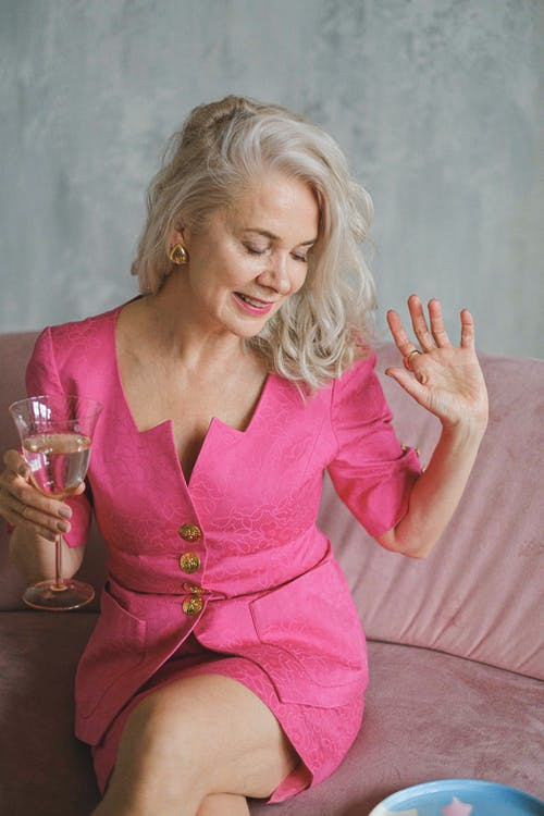 Woman in Pink V Neck Long Sleeve Dress Holding Clear Drinking Glass