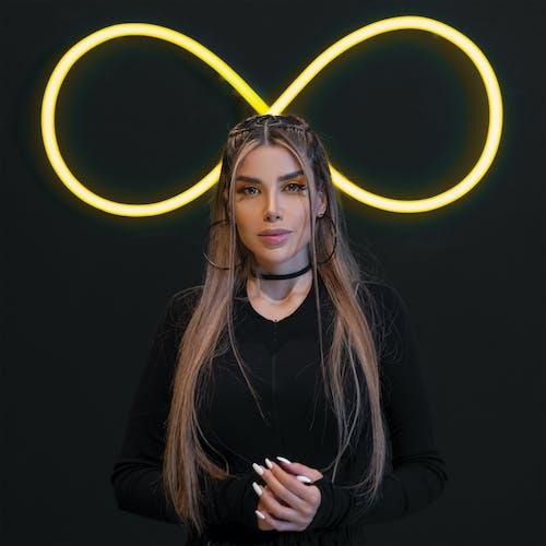 Woman near black wall with neon light