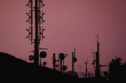 Silhouette of People Standing on Electric Tower during Sunset