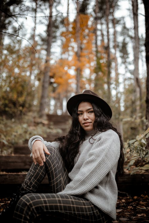 Woman in Black Hat and Gray Sweater Sitting on Brown Wooden Bench