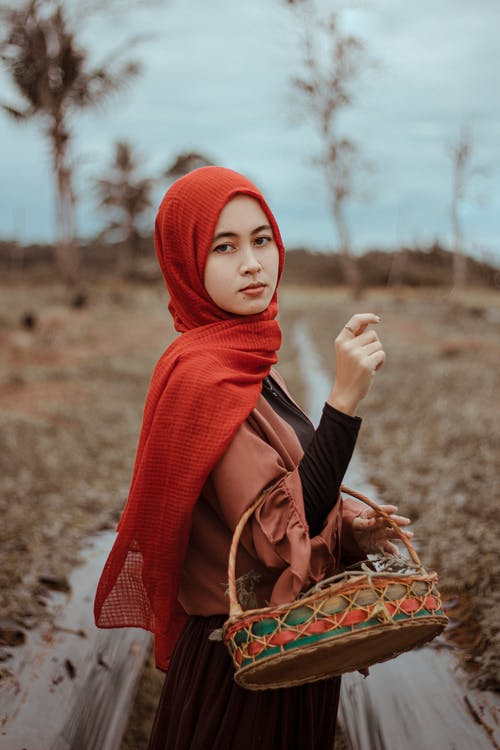 Woman in Red Hijab Holding Brown Wicker Basket