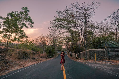 Woman in Red Dress Walking on Road