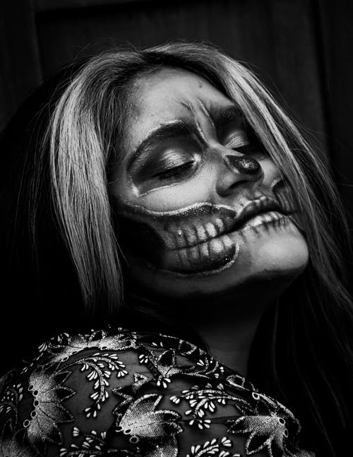 Grayscale Photo of a Woman in Floral Shirt with Spooky Face Paint