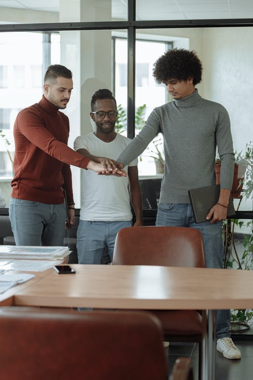 Men in the Office Standing While Hands Together