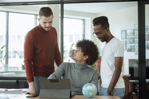 Man in Gray Shirt Explaining Work to Colleagues
