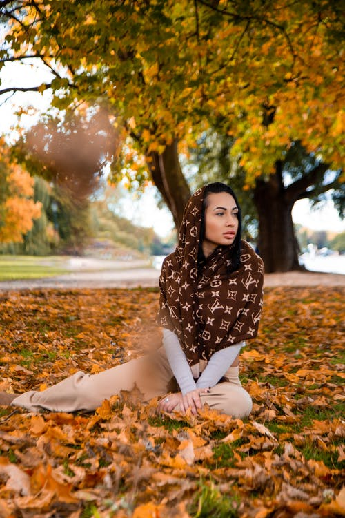 Woman with Louis Vuitton Scarf Sitting on Fallen Leaves