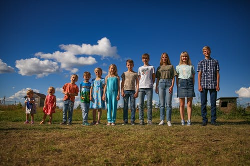 Group of People Standing on Green Grass Field