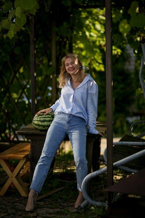 Woman in Blue Denim Jacket Sitting on Brown Wooden Bench