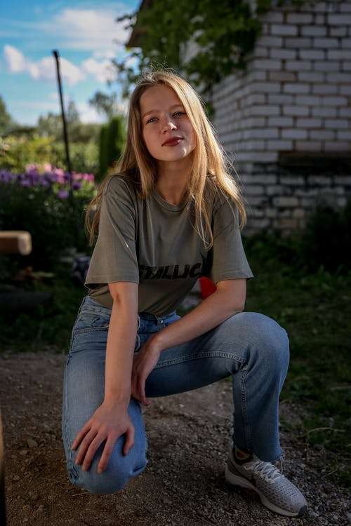 Woman in Brown Crew Neck T-shirt and Blue Denim Jeans Sitting on Brown Wooden Bench
