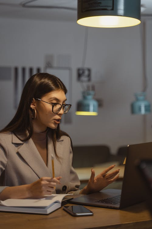 Woman in White Blazer Using Black Laptop Computer