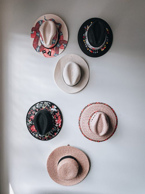 Collection of various stylish hats hanging on white wall near window in daytime